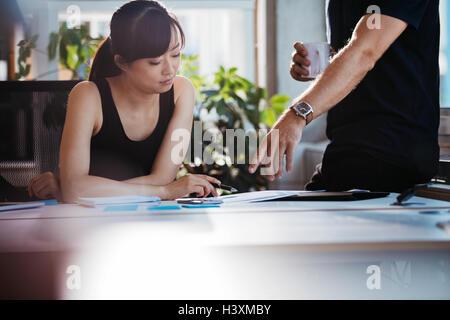 Deux jeunes cadres la discussion de nouvelles idées d'affaires dans le bureau. Des collègues qui travaillent ensemble sur la paperasse. Femme assise à son des