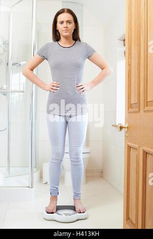 Adolescente malheureuse debout sur un pèse-personne Banque D'Images