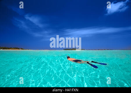 Jeune homme snorkling en lagune tropicale avec des bungalows sur pilotis Banque D'Images