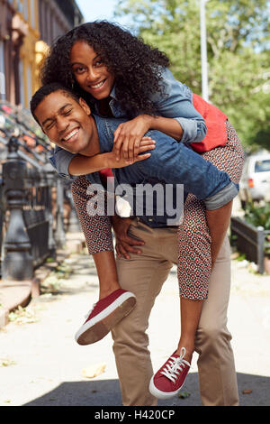 Man carrying woman piggyback sur les trottoirs de la ville Banque D'Images