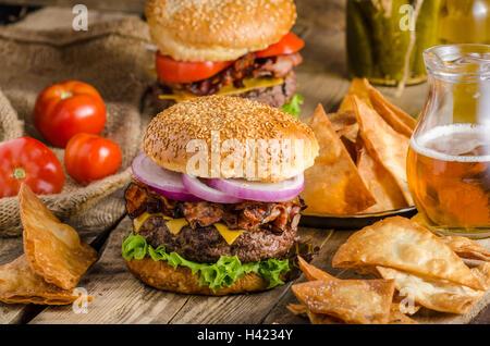 American burger bacon rustique avec du boeuf, cheddar, salade et légumes, vieille photo d'école, avec de la bière Banque D'Images