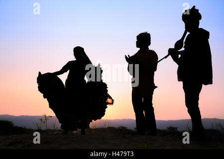 Coucher du soleil, la silhouette d'une femme dansant une danse traditionnelle avec deux musiciens, Pushkar, Rajasthan, Banque D'Images