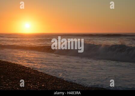 Les vagues déferlent sur le rivage avec un coucher de soleil orange vif Banque D'Images