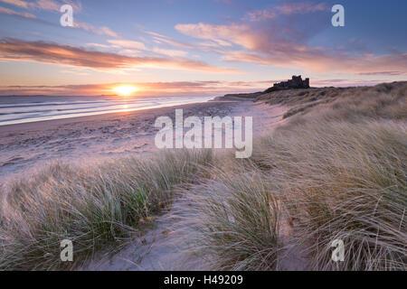 Lever de soleil sur plage de Bamburgh et Château des dunes de sable, Northumberland, Angleterre. Printemps (mars) Banque D'Images