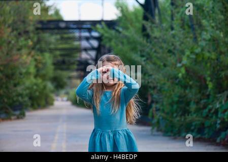 Happy little girl making heart shape geste sur un pont Banque D'Images