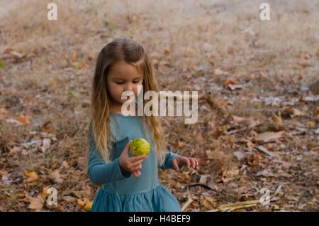 Little girl holding a petite citrouille dans sa main Banque D'Images