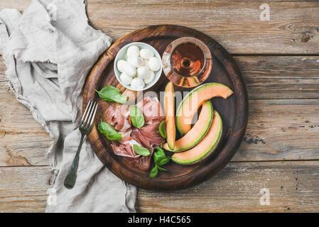 Jambon, melon, mozzarella et d'un verre de vin dans le bac en bois Banque D'Images
