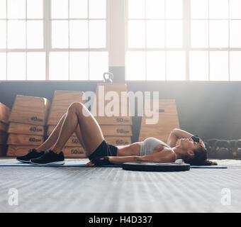 Jeune femme allongée sur le dos dans la salle de sport après son entraînement. Femme de remise en forme pour se Banque D'Images