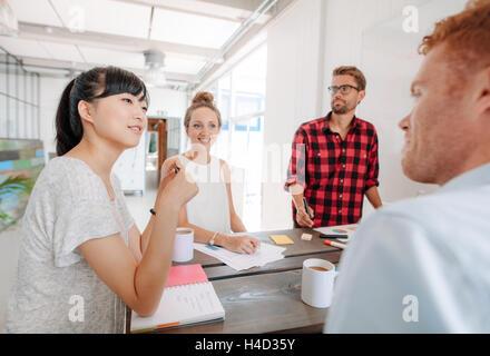 Divers groupes de jeunes gens d'affaires à sa présentation dans l'office. Les collègues assis autour d'une table Banque D'Images
