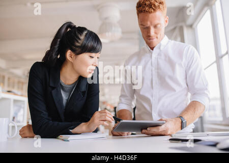 Les gens d'affaires travailler ensemble sur digital tablet in modern office. Business man and woman standing at Banque D'Images