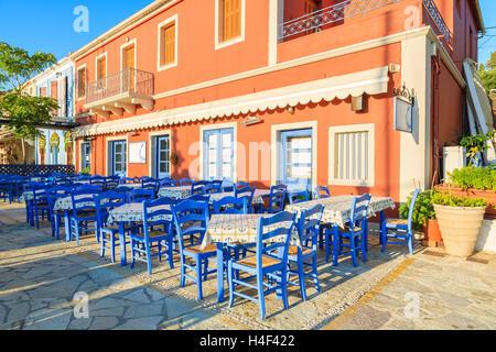 Chaises bleues avec des tables en face de taverne grecque traditionnelle à Fiskardo port, l'île de Céphalonie, Grèce Banque D'Images