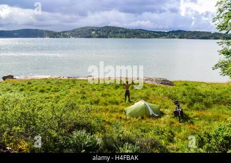 Homme debout près de tente de camping après en Suède (Orust) Banque D'Images