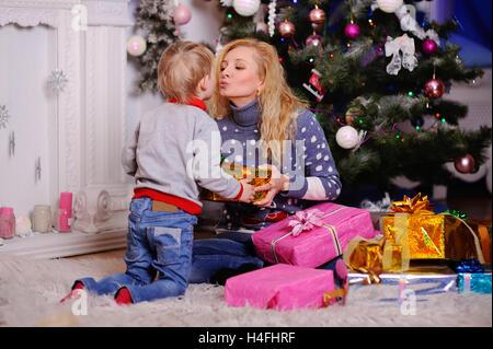 Maman donne un petit enfant un cadeau de Noël sur l'arbre de Noël arrière-plan. Des cadeaux de Noël. Bisous fils Banque D'Images
