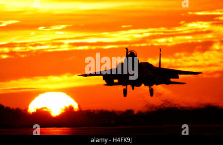 F-15E Strike Eagle United States Air Force à l'atterrissage à RAF Lakenheath Suffolk UK contre un coucher de soleil orange