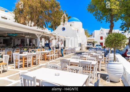 La ville de Mykonos, Grèce - 16 MAI 2016: hommes parler grec dans une taverne typique avec des chaises et tables Banque D'Images
