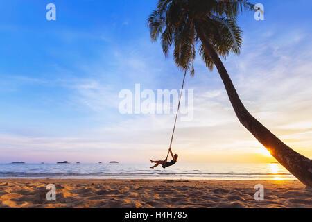 Jeune femme heureuse de vous détendre sur une balançoire attaché à un palmier sur un paradis plage au coucher du Banque D'Images