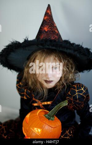 L'Halloween. Girl portrait sorcière maléfique.Il est vêtu de noir et orange robe et chapeau. En vertu de son chapeau Banque D'Images