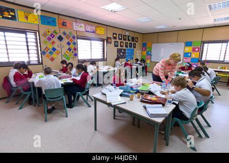 Les enfants de l'école junior avec enseignante de se concentrer sur leurs études à leur bureau dans la classe de Banque D'Images