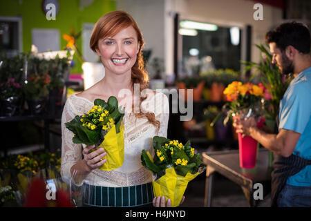 Woman holding flower bouquet tandis que l'homme travaillant dans l'arrière-plan
