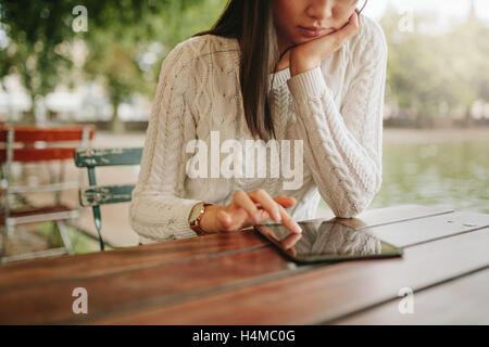 Young woman using digital tablet at outdoor cafe. La navigation sur les pages du site web féminin touch pad en dans Banque D'Images