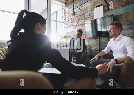 Jeune homme assis en train de discuter affaires avec des collègues. Les professionnels en salle de réunion. Banque D'Images