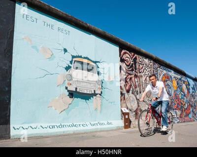 Les cycles de l'homme passé peinture de voiture Trabant sur mur de la East Side Gallery à l'ancien mur de Berlin Banque D'Images