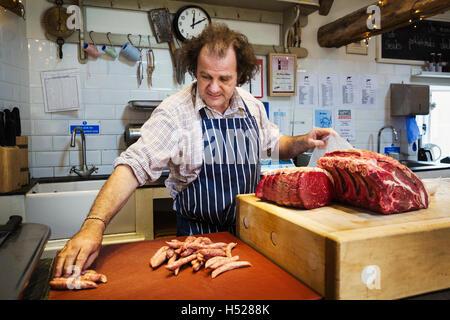 Boucher la préparation d'un grand morceau de boeuf dans une butcherer's shop. Banque D'Images