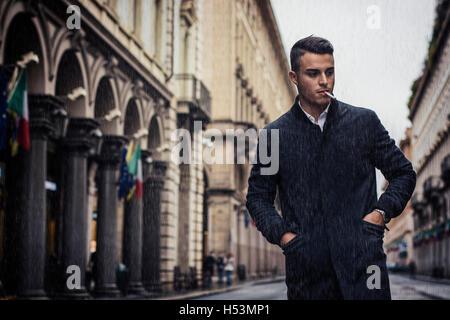 Toute la longueur du jeune homme en manteau de marcher sous la pluie le long de la rue de ville holding cigarette. Banque D'Images