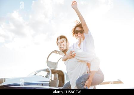 Happy young couple having fun sur la piste à l'aéroport Banque D'Images