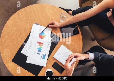 Vue de dessus de deux personnes qui travaillent avec les graphiques autour de table. Femme et homme d'affaires en Banque D'Images