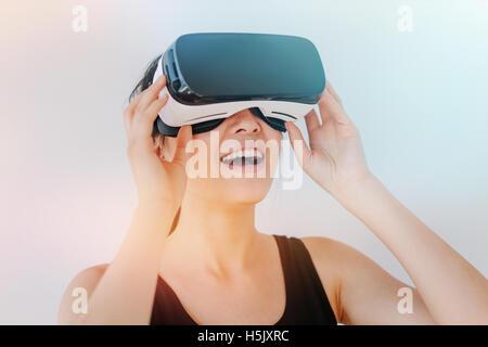 Close up shot of young woman en utilisant les lunettes de VR contre l'arrière-plan gris avec effet sunflare. Modèle Banque D'Images