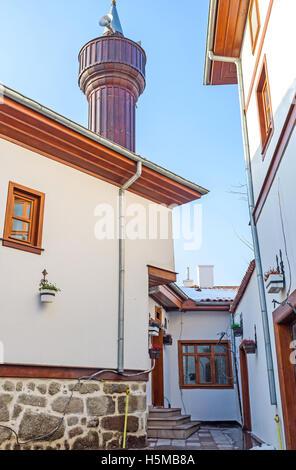Le nouveau minaret en bois blanc se lève sur les cottages dans le quartier restauré du village turc, Ankara, Turquie. Banque D'Images