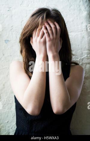 Jeune femme se cachant le visage avec les mains Banque D'Images