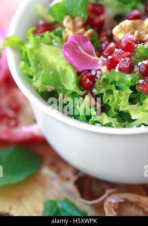 Close up de salade frisée avec grenade, noix, pétales de rose, la menthe poivrée, l'huile d'olive, le vinaigre balsamique et le sel