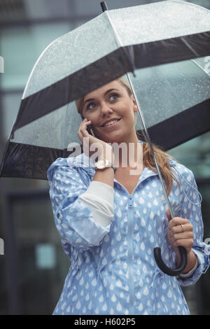 Beautiful woman holding umbrella while talking on mobile phone Banque D'Images