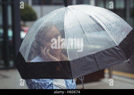 Woman holding umbrella while talking on mobile phone Banque D'Images