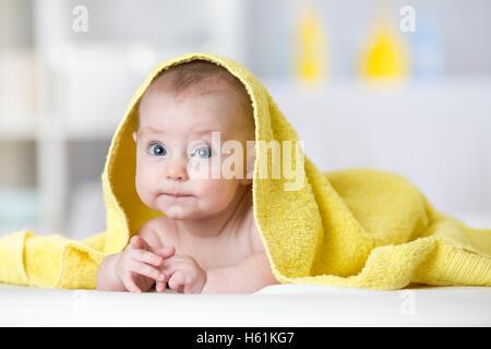 Serviette bébé fille sous dans la chambre après le bain ou douche. Literie et textile pour les enfants. Banque D'Images