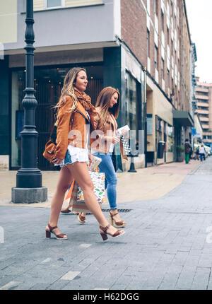 Deux femmes holding shopping bags marcher dans la ville Banque D'Images