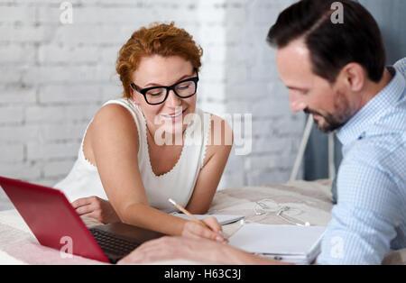 Femme faisant quelques notes dans l'ordinateur portable de l'homme Banque D'Images