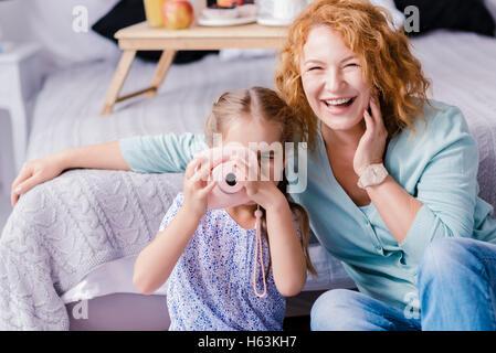 Petite-fille de rire en prenant des photos avec sa grand-mère Banque D'Images