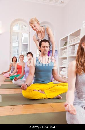 Groupe de personnes dans un studio de yoga sitting in Lotus pose tandis que se redresse le dos de l'instructeur Banque D'Images