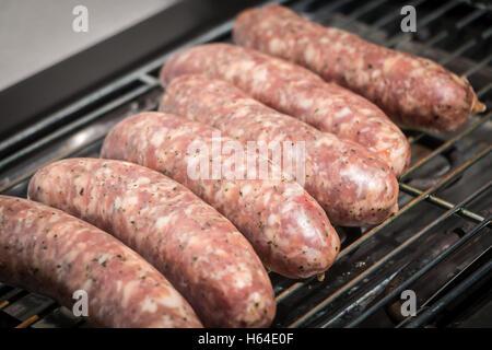 Herbes à cuire des saucisses sur un barbecue électrique en été Banque D'Images
