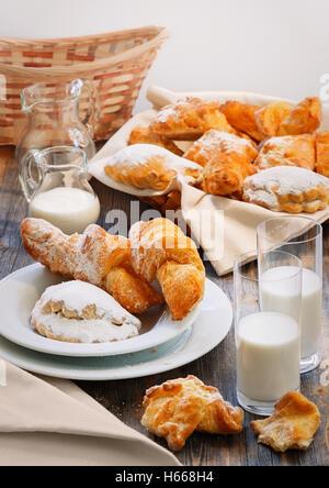 Tartes sucrées, jug et verres avec du lait dans un cadre rustique de style Banque D'Images