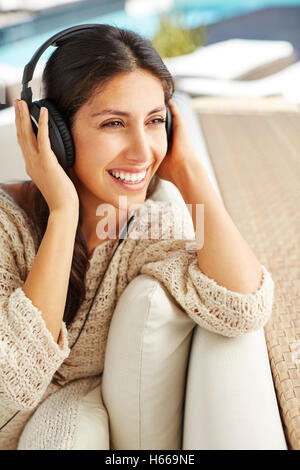 Smiling woman listening to music with headphones on sofa Banque D'Images