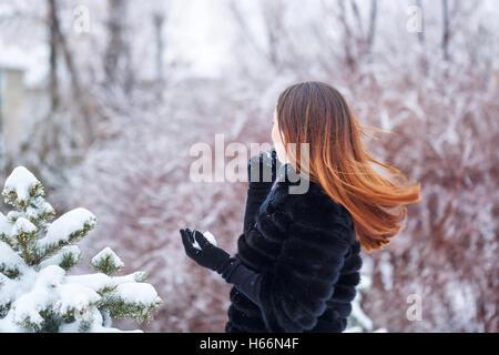 ... Sweet jolie fille dans un manteau de fourrure et des gants dans le parc  d  59d86299856