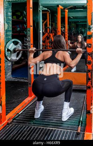 Femme dans la salle de sport la levée de poids Banque D'Images