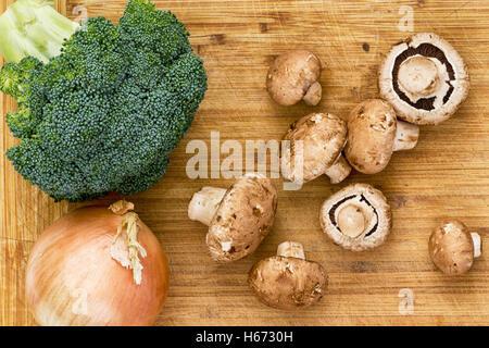 Vue du haut vers le bas sur les champignons, le brocoli et l'oignon prêt à être préparé plus de planche à découper Banque D'Images