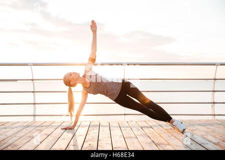 Remise en forme sportive woman doing yoga bordé à l'extérieur à l'exercices beach pier Banque D'Images
