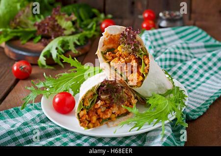 Burritos wraps avec la viande hachée et de légumes sur un fond de bois. Banque D'Images