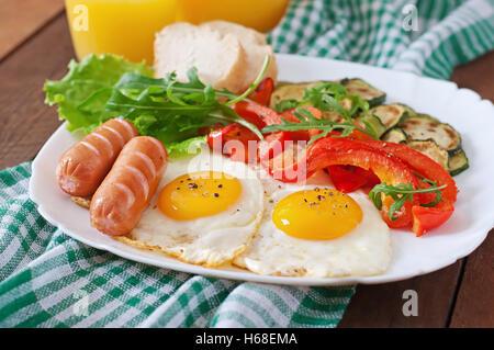 Petit-déjeuner anglais - les œufs, saucisses, courgettes et poivrons. Banque D'Images
